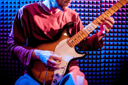 Young man playing on the guitar in sound recording studio.