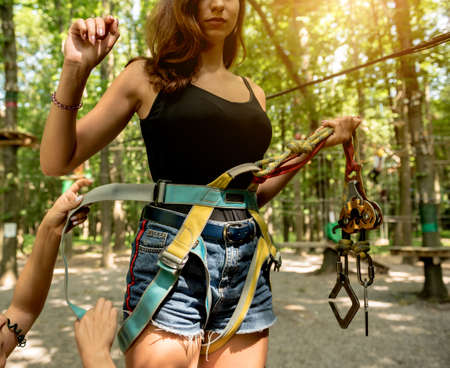 Young woman in adventure rope park. Climbing Equipment. Фото со стока