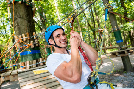 Young man in adventure rope park. Climbing Equipment.
