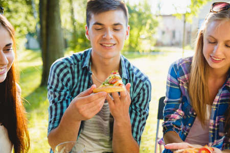 Cheerful friends on picnic in the park. Eating pizza