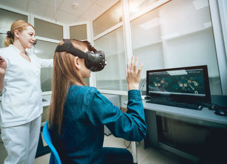 Ophthalmology doctor checks the girls vision with virtual reality goggles. Stockfoto