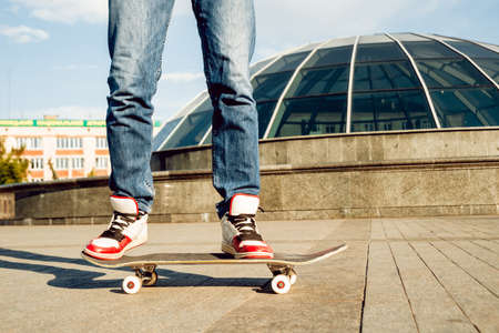 Young man riding a skateboard. Town Square. 免版税图像