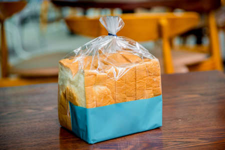 Sliced bread, wrapped in plastic. Bakery background.