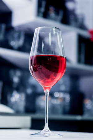 Red wine in a glass at restaurant. Light background. Banco de Imagens