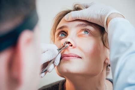 Otolaryngologist examines womans nose with nasal dilator.