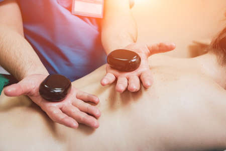 Hot stone massage therapy. The therapist massages the womans back. 写真素材