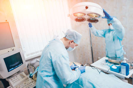 Surgeon and assistant in operating room with surgery equipment. 写真素材