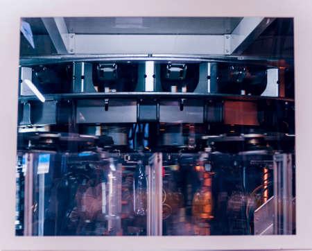 Automatic filling machine pours water into plastic PET bottles.