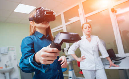 Ophthalmology doctor checks the girls vision with virtual reality goggles. 写真素材