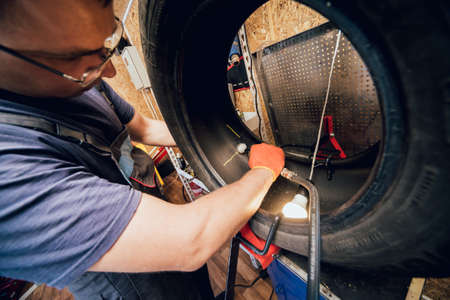 Professional car mechanic replace tire on wheel.