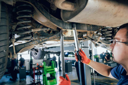 Car mechanic examining car suspension of lifted automobile
