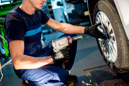 Professional car mechanic working with in auto repair service. Repair of wheels
