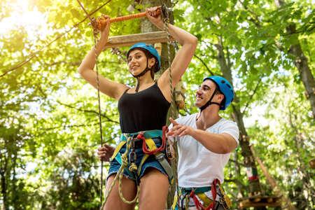 Young couple having fun time in adventure rope park. Foto de archivo