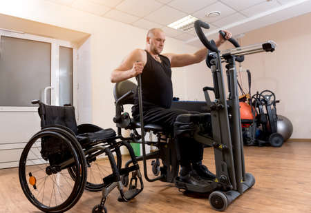Disabled man training in the gym. Rehabilitation center