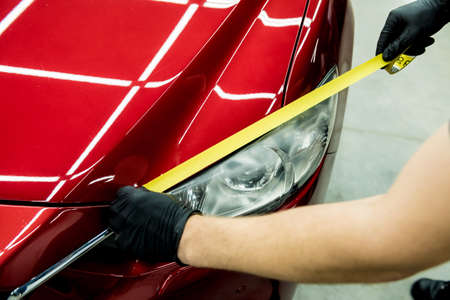 Car service worker applying protective tape on the car details before polishing. Stockfoto