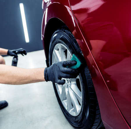 Car service worker polishing car wheels with microfiber cloth. Stockfoto