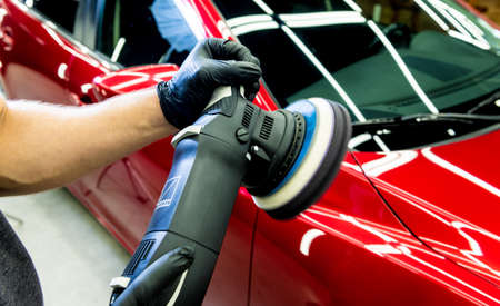 Car service worker polishes a car details with orbital polisher. Stockfoto