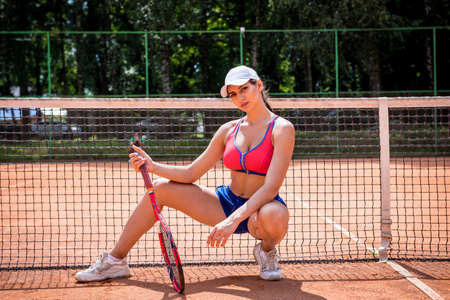 Portrait of young athletic woman on tennis court. Stockfoto