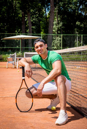 Portrait of young athletic man on tennis court.