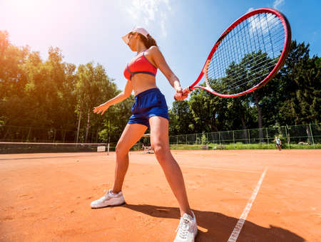 Young athletic woman playing tennis on the court.