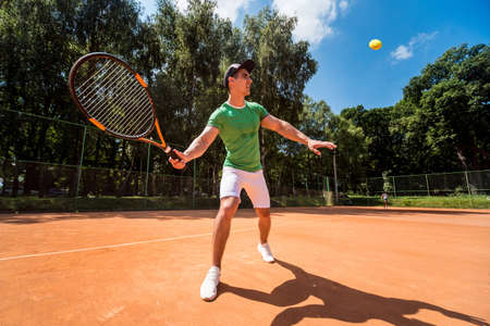 Young athletic man playing tennis on the court.