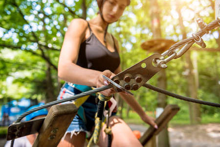 Young woman in adventure rope park. Climbing Equipment. Stockfoto