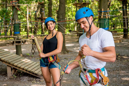 Young couple having fun time in adventure rope park.