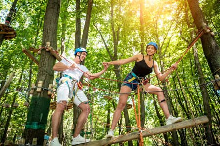 Young couple having fun time in adventure rope park. Banque d'images