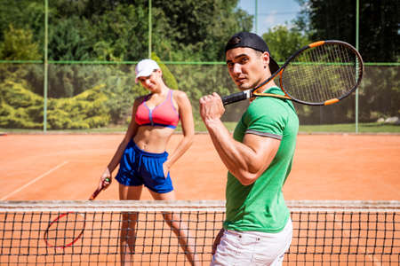 Young athletic couple playing tennis on the court.