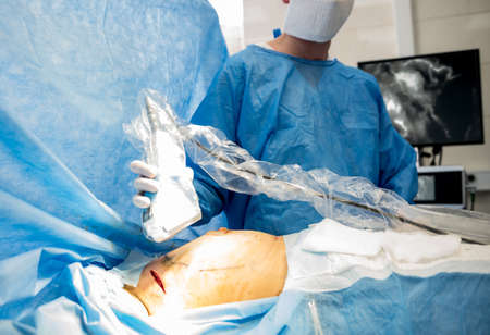 The surgeon uses a portable fluorescence imaging device during removal.
