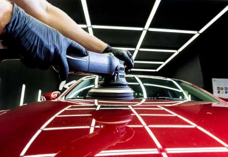Car service worker polishes a car details with orbital polisher. 版權商用圖片