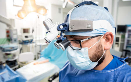 Spinal surgeon in operating room with surgery equipment.