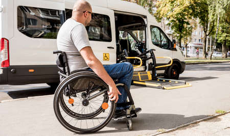 A man in a wheelchair moves to the lift of a specialized vehicle
