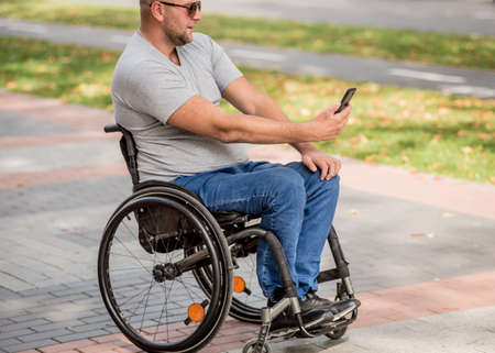 Handicapped man in wheelchair at the park alley use a smartphone Stock fotó
