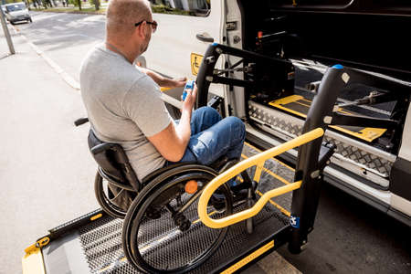 A man in a wheelchair on a lift of a vehicle for people with disabilities