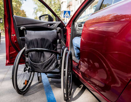 Young handicapped man on drivers seat of his car