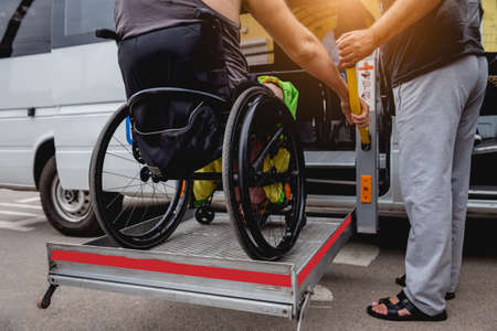 Disabled man on wheelchair using accessible vehicle with lift mechanism.