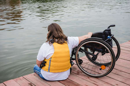 People with disabilities in life vests on the pier.