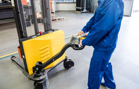 A worker in a warehouse uses a hand pallet stacker to transport pallets.