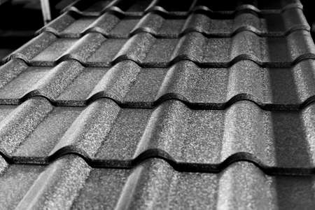 Gray metallic roof tiles background with light pattern.