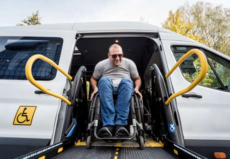 A man in a wheelchair on a lift of a vehicle for people with disabilities Standard-Bild