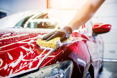 Worker washing red car with sponge on a car wash