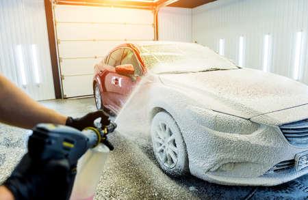 Worker washing car with active foam on a car wash. Standard-Bild