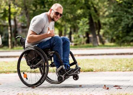 Handicapped man in wheelchair walk at the park alley