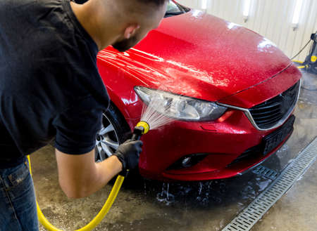 Service worker washing car on a car wash.