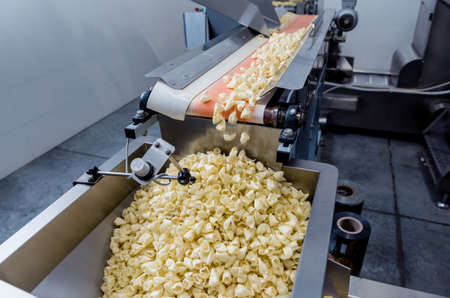 Conveyor line for packing snacks and chips in a modern factory