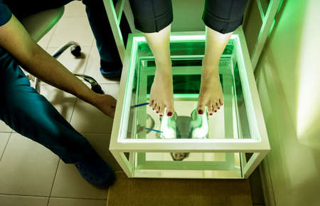 Doctor is at examining womans feet by using plantoscopy device