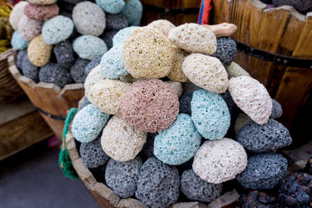 Colored pumice stones for foot care in the wooden baskets on the street market