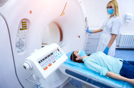 Radiologist with a female patient in the room of computed tomography