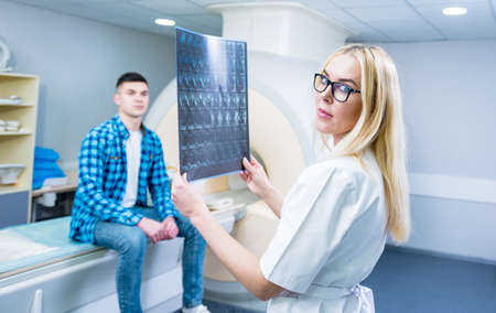 Radiologist with a male patient examining a mri scan